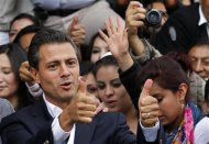 Enrique Pena Nieto presidential candidate of the Institutional Revolutionary Party (PRI) shows his inked thumbs after voting in Atlacomulco July 1, 2012. REUTERS/Tomas Bravo