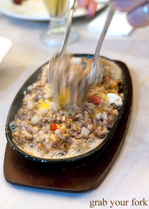 mixing the egg yolk into the sisig at lamesa phillipine cuisine haymarket chinatown