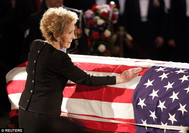 Nancy Reagan touches the casket of her husband, former U.S. President Ronald Reagan, as it lies in state in the rotunda of the United States Capitol in Washington, June 9, 2004
