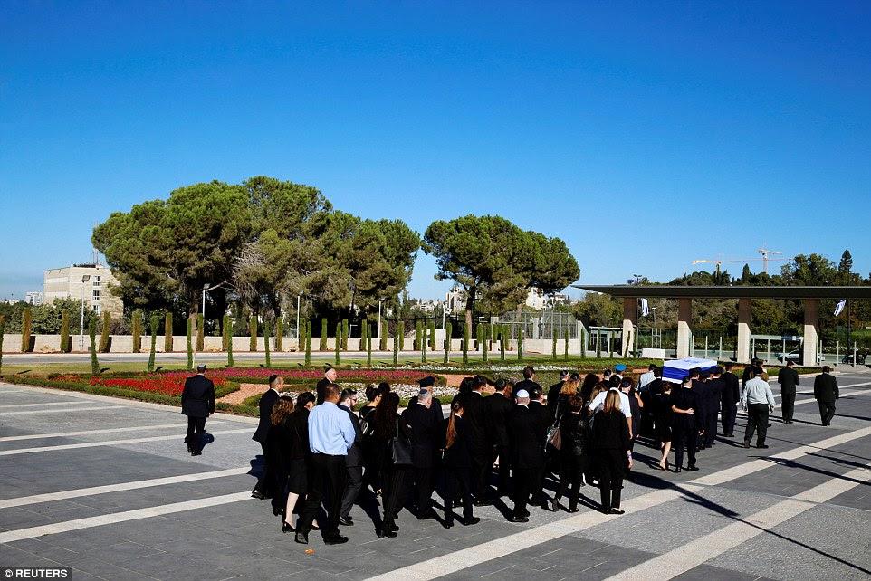 Movendo: famaily Peres 'segurar um ao outro enquanto eles seguem o caixão do estadista em sua viagem para o seu lugar de descanso final