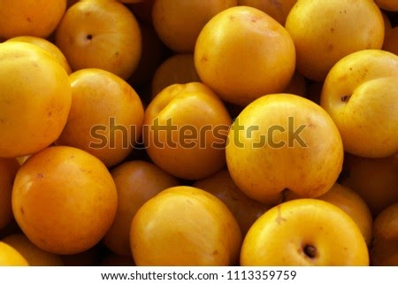 Golden yellow, fresh and healthy plums at the market.. also known as mirabelle plums.. They are small...