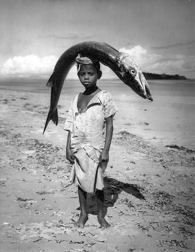 Boy carrying fish