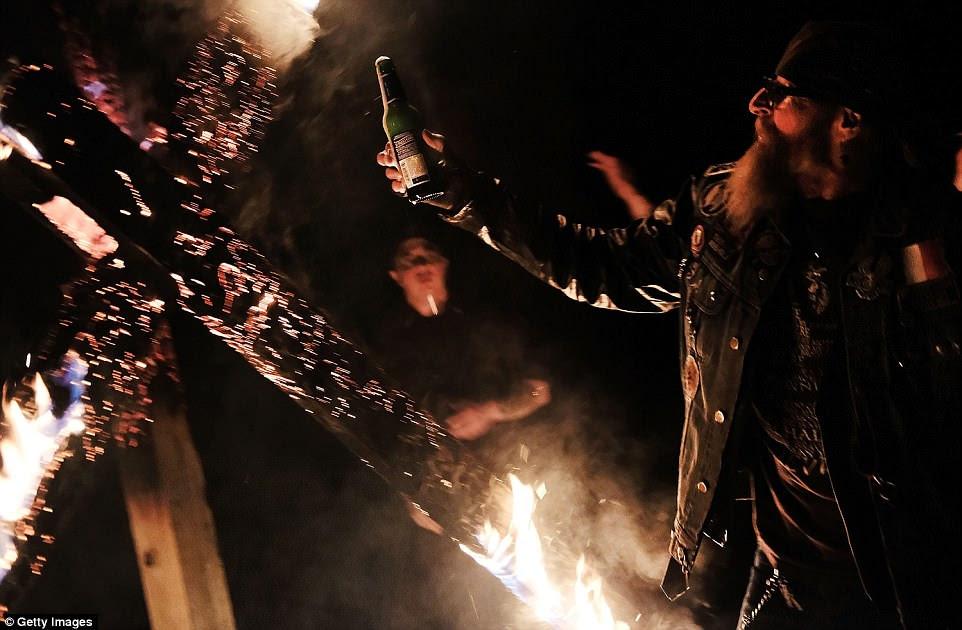 Un miembro del Movimiento Nacional Socialista sube una cerveza para brindar por una esvástica ardiente durante la ceremonia de la noche del sábado