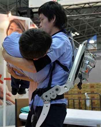 Traje com ar comprimido em um tanque que fica nas costas é muito prático e dá poder extra a cuidadores para  levantar um paciente acamado  (AFP PHOTO / Yoshikazu TSUNO )