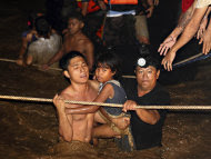 Residents are rescued by volunteers following a flash flood that inundated Cagayan de Oro city, Philippines, Saturday, Dec. 17, 2011. A tropical storm triggered flash floods in the southern Philippines, killing scores and missing more. Mayor Lawrence Cruz of nearby Iligan said the coast guard and other rescuers were scouring the waters off his coastal city for survivors or bodies that may have been swept to the sea by a swollen river. (AP Photo/Erwin Mascarinas)