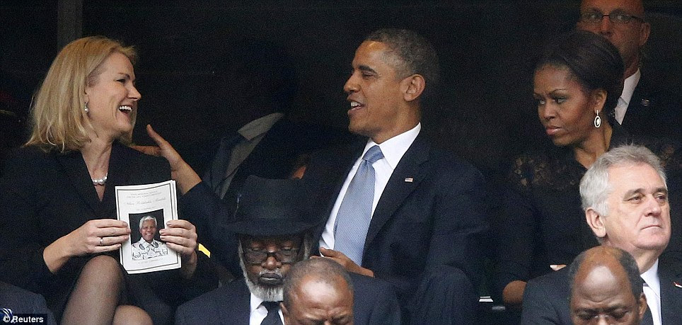Obama and the Danish Prime Minister share a joke during the memorial service as the First Lady looks on unimpressed