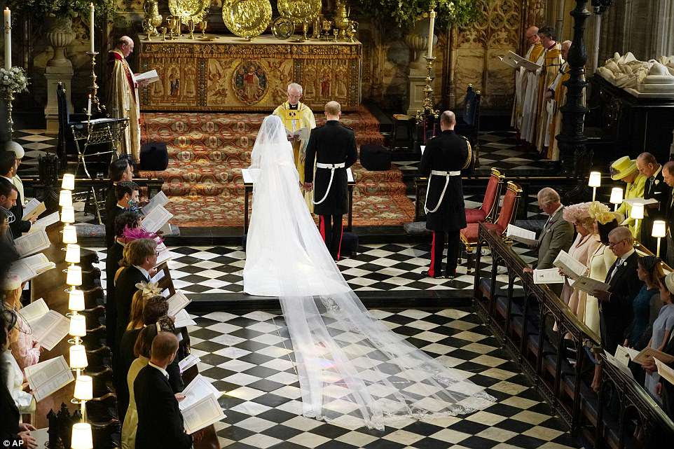El tren del vestido de Meghan se arrastra por el pasillo mientras ella y el Príncipe Harry se paran frente al Arzobispo Justin Welby
