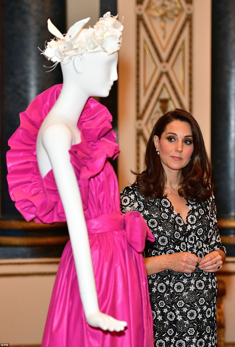 A Duquesa de Cambridge inspeciona um conjunto de rosa de néon enquanto ela e Sophie recebem o lançamento do Commonwealth Fashion Exchange no Buckingham Palace's Music Room