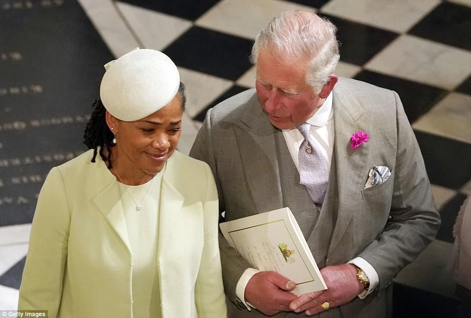 El príncipe Carlos, sosteniendo una copia del orden del servicio, habla con Doria Ragland, la madre de la novia, en la capilla