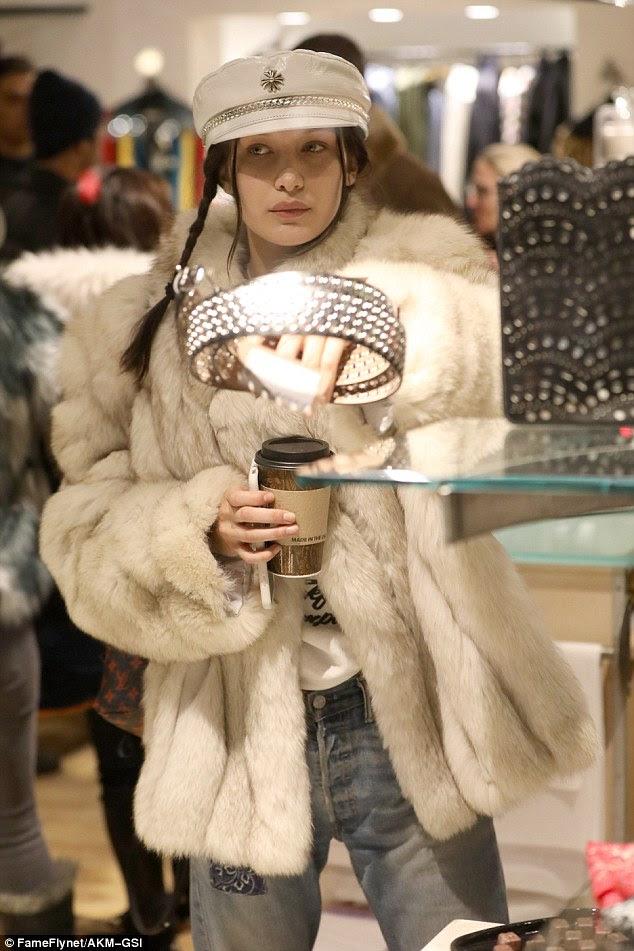 Chapéus fora;  Bella parecia elegante em uma capa de estilo militar com detalhes em cadeia