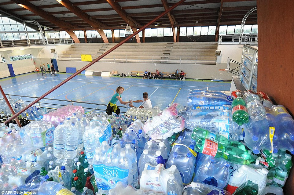 People carry bottles of water as they organise a help area in the central Italian village of Amatrice