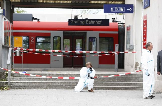 A police officer takes pictures at the train station in Grafing, Germany, May 10, 2015. A man attacked passengers with a knife at a train station in the Munich area in southern Germany early on Tuesday, leaving four people with life-threatening injuries, Bavarian radio reported. REUTERS/Michaela Rehle