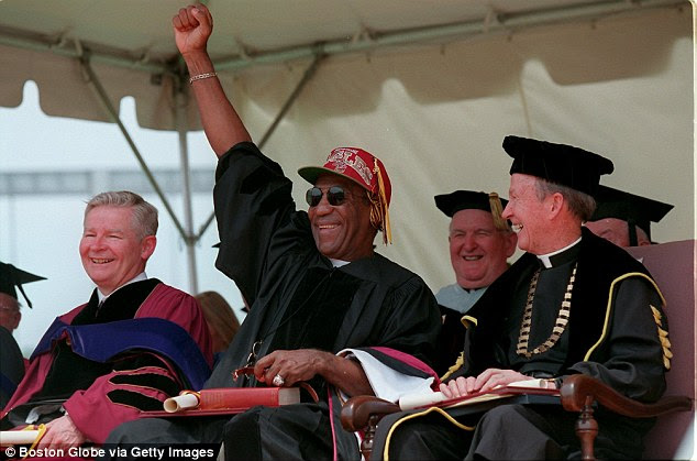 Role model no more: Flanked by Boston College President Reverend J. Donald Monan (right) and UMass President William M. Bulger, actor Bill Cosby reacts to the graduates at Boston College commencement exercises in 2011. UMass cut all ties with Cosby this week
