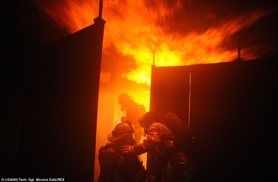 Training: Members of the 106th Rescue Wing's fire department train on various fire-suppression systems as they battle a blaze at the Suffolk County Fire Academy in Yaphank, New York