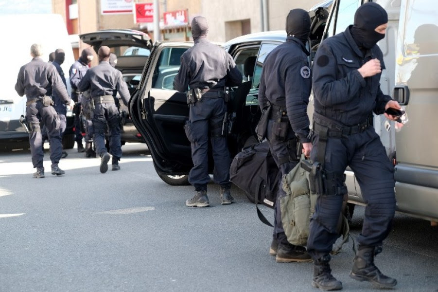 French National Gendarmerie Intervention Group (GIGN) stand next to vehicles as they gather outside the Super U supermarket in the town of Trebes, southern France, where a man took hostages killing at least two before he was killed by security forces on March 23, 2018. Security forces killed a gunman who first hijacked a car in nearby by Carcassonne, killing a passenger and injuring the driver, before shooting a policeman who was out jogging with his colleagues nearby. He then drove to a Super U supermarket in the town of Trebes and holed up there for more than three hours with hostages, killing at least two other people, according to sources. ERIC CABANIS / AFP