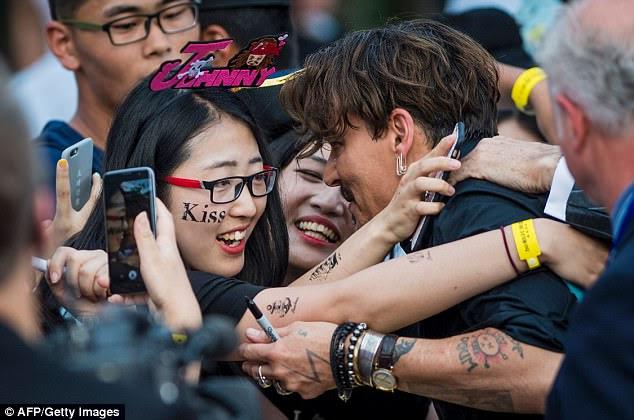 Beije-me rápido!  Um fã sortudo recebeu um abraço quente de Johnny apesar de sua segurança tentando puxá-lo de volta