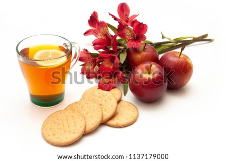 Side view of digestive biscuits, tea, apple and flower on a white background. Still life photography, waiting for autumn and Fall Harvest. Nice warm colors and nostalgic mood.
