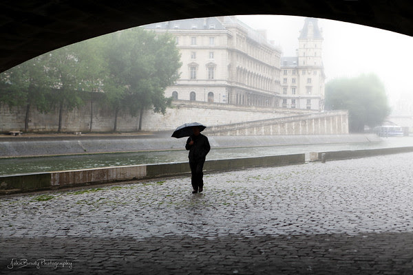 A Little Rain Gives Solitude To A Stroller - At Pont Neuf Bridge, an area usually swarming with people, on the Banks of the River Seine in Paris, France - JohnBrody.com - JohnBrody.blogspot.com