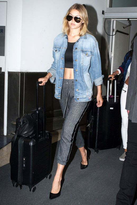 Le Fashion Blog Airport Style Gigi Hadid Elevated Athleisure Look Aviator Sunglasses Denim Jacket Black Crop Top Grey Joggers Pumps Via Harpers Bazaar