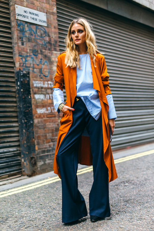 Le Fashion Blog Street Style Lfw Blonde Wavy Hair Layered Look Orange Trench Coat Oversized Blue Top With Statement Sleeves Navy Wide Leg Pants Black Boots Via Olivia Palermo