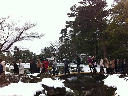 Tourists crossing the Niji (rainbow) bridge at Kenroku-en