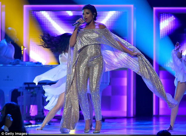 She's super! The singer wowed in the silvery jumpsuit and cape onstage