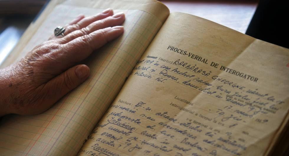 Una mujer consulta un informe de la Securitate rumana.