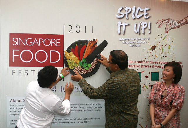 Mr S. Iswaran (with Chef Milind Sovani assisting) placing the final piece on SFF's new logo