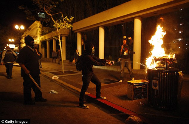 Violent: In Oakland, as rallies stretch into the night, protesters light a trash can on fire during a May Day
