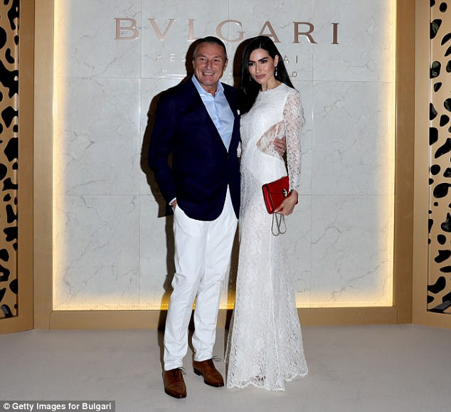 Looking good: Bulgari CEO Jean-Christophe Babin wore a pair of winter white trousers with a navy blue blazer alongside Diala Makki in a gorgeous white dress