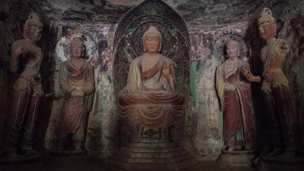 In a Mogao cave, lit by the flashlight of a guide, a Buddha statue surrounded by disciples dating from the China's Tang ...