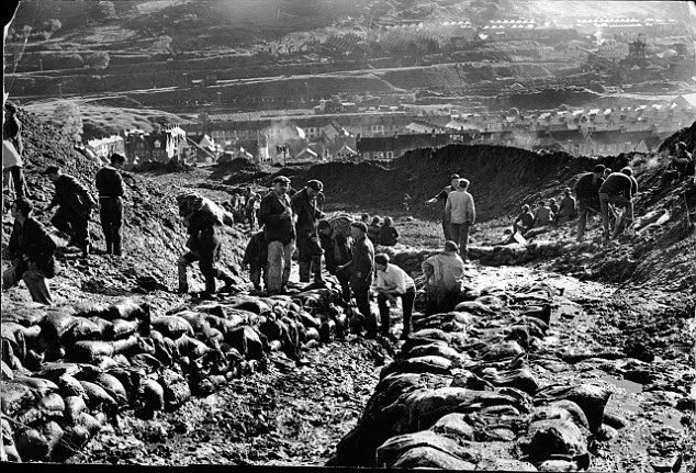 Volunteers are pictured working to safeguard the coal tip in the 1960s to prevent further slides