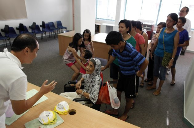"People queue up for free N95 masks at a distribution centre in Singapore June 23, 2013. One million N95 masks will be given to the poorest 200,000 households for free by the government starting from Sunday, according to authorities. The ""haze"" caused by fires in Riau province on Indonesia's Sumatra island has shrouded neighbouring Singapore but air quality in the city state improved over the weekend after reaching hazardous levels. REUTERS/Edgar Su (SINGAPORE - Tags: ENVIRONMENT HEALTH)"