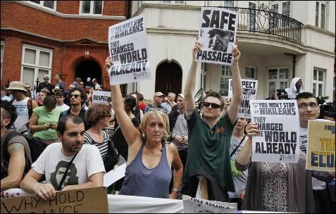 Seguidores del fundador de WikiLeaks, el australiano Julian Assange, escuchan sus declaraciones a la entrada de la embajada de Ecuador en Londres.