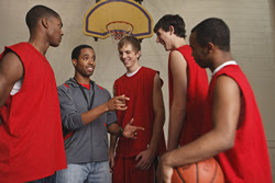Photo: Male teen basketball players talking to their coach