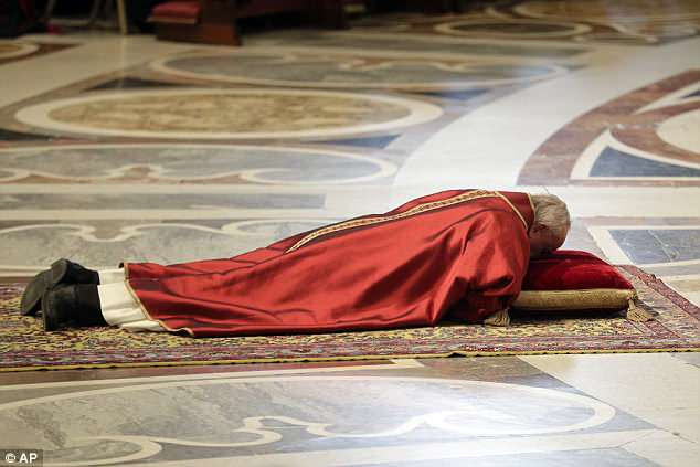 Pope Francis lies down in prayer during the Good Friday Passion of Christ Mass, inside St. Peter's Basilica, at the Vatican earlier on Friday