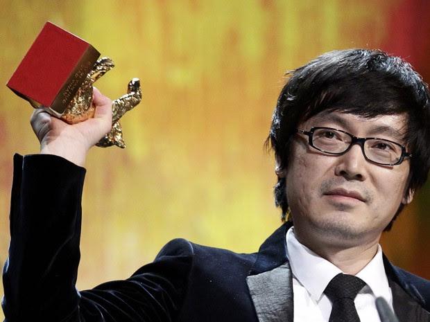 O diretor Diao Yinan regura o urso de ouro durante a premiação neste sábado (15) (Foto: Tobias Schwarz/Reuters)