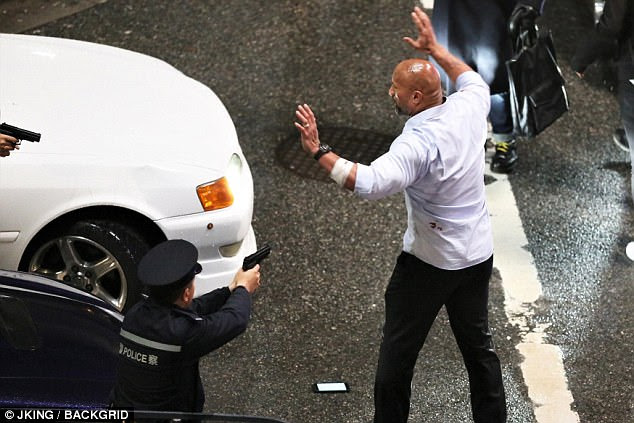Surrender: The movie star was standing with his hands up  as two cops advance on him, one of them training a gun on him