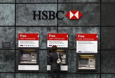 Μια γυναίκα χρησιμοποιεί ένα μηχάνημα ανάληψης μετρητών σε τράπεζα HSBC στην πόλη του Λονδίνου 28 Φεβ. 2011.  REUTERS / Andrew Κερδίζοντας
