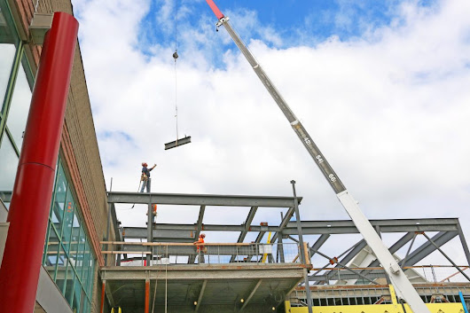 Goodman's signature beam hoisted into place