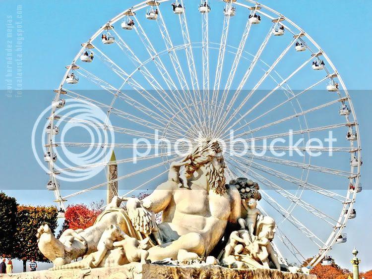 Imagen de escultura al aire libre de estilo greco-latino con la noria y el puntiagudo obelisco detrás, ubicados en los Campos Elíseos de París (Francia)
