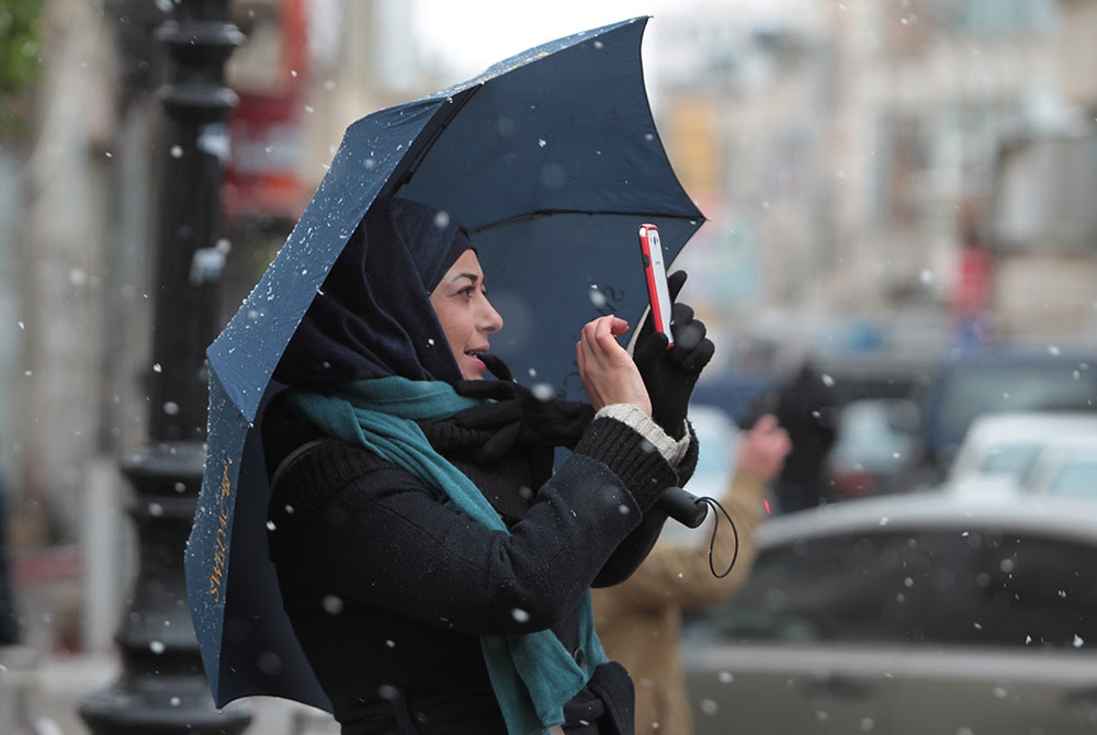 A Palestinian woman takes pictures with her mobile of the snowfall in the West Bank city of Ramallah. (AFP/Getty Images)