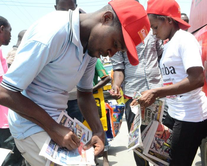 14.Mpenzi msomaji wa Uwazi aliyejitambulisha kwa jina la,Haidary Rashid (kushoto) akijaza kuponi yake baada ya kununua gazeti kwa muuzaji ili kushiriki droo ya pili.-001
