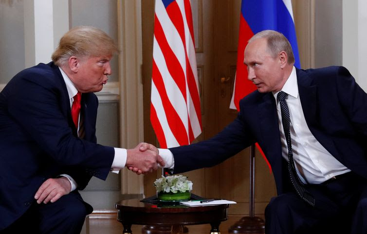 U.S. President Donald Trump and Russia's President Vladimir Putin react as they shake hands during their meeting in Helsinki, Finland July 16, 2018. REUTERS/Kevin Lamarque