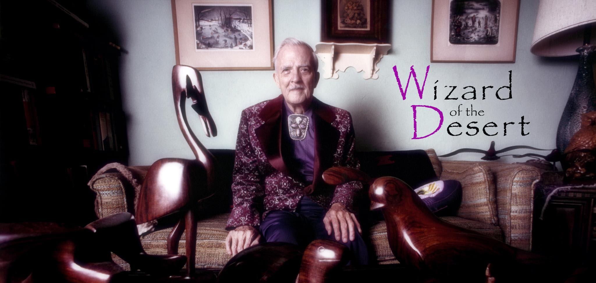 """FOTO: Dr. Milton Erickson, sentado, e uma inscrição na lateral direita com a frase: """"Wizard of the Desert""""."""