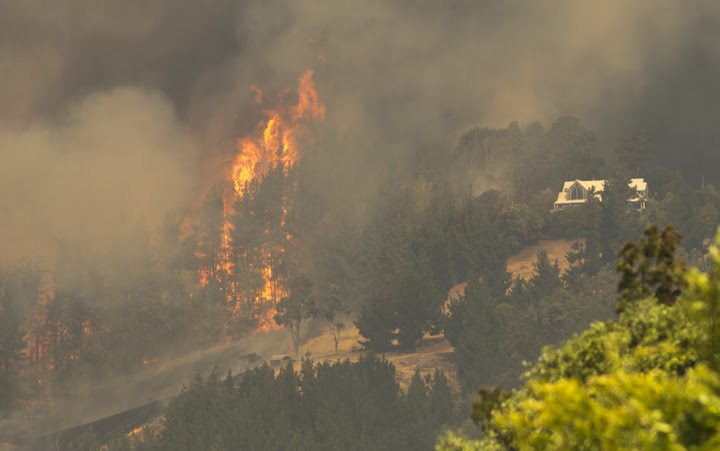 Flames leap close to a house in the Port Hills.