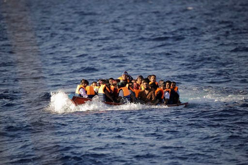 Migrants and refugees fleeing Libya with their dinghy floating low in the water before being helped by members of a Spanish NGO, during a rescue operation at the Mediterranean sea, about 25 miles north of Sabratha, Libya, Thursday, Aug. 18, 2016. At least three people have died on Thursday morning during the sinking of a wooden boat full with migrants as they tried to reach the Italian coasts. (AP Photo/Emilio Morenatti)