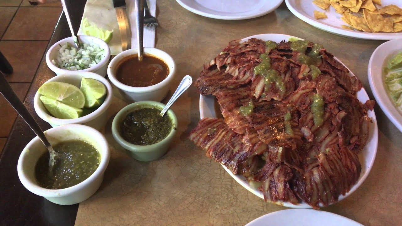 Foto mostrando un plato de nachos de pastor y diferentes salsas en la mesa