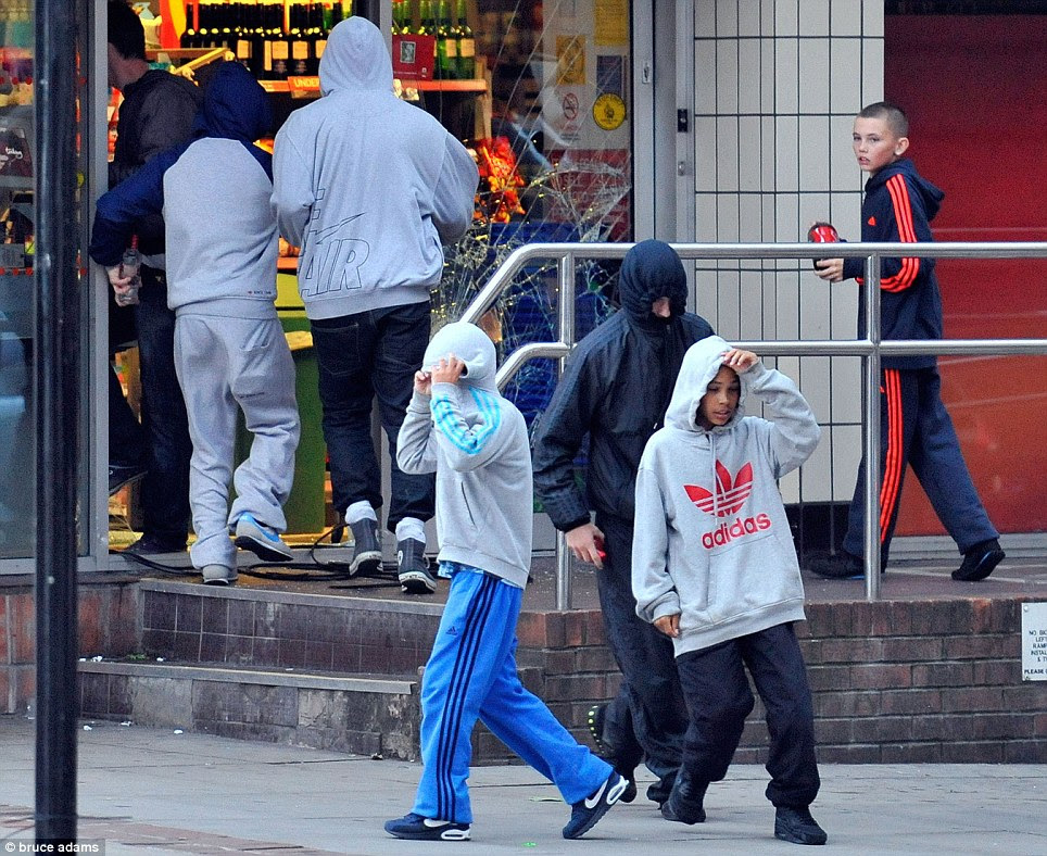 Primary school age: Two youngsters pull the hoods from their baggy sweaters over their heads as they stand outside the looted store. The child who stole a bottle of wine is seen behind them returning with a bottle of coke
