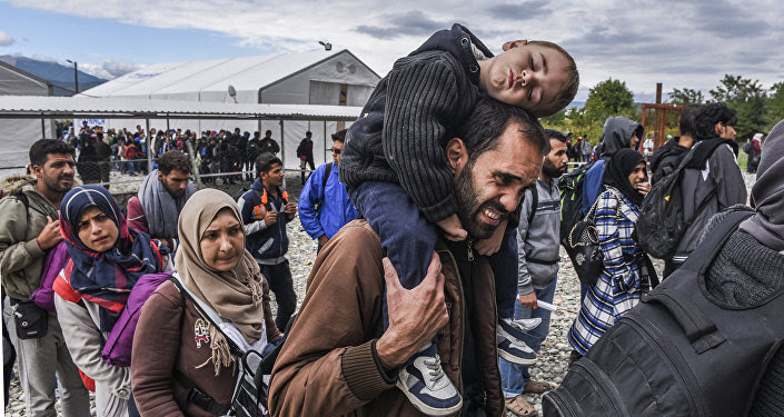 Migrants and refugees stand in line as they wait to board a train at the registration camp after crossing the Macedonian-Greek border near Gevgelija on September 28, 2015
